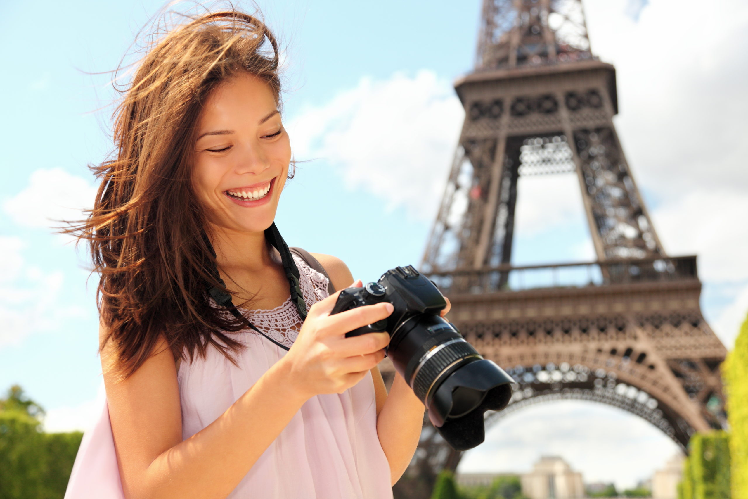 Paris Eiffel Tower tourist with camera taking pictures in front of the Eiffel tower, Paris, France. Young photographer woman in her 20s. Candid.
